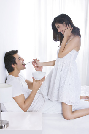 Side view of romantic woman feeding man in bed