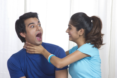 Playful young woman gripping mans neck at home