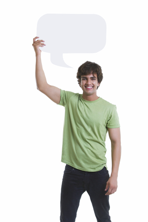Portrait of handsome young man holding speech bubble over white background Stock Photo