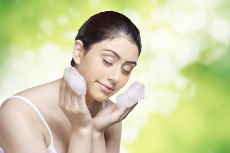 Beautiful young woman applying soap sud on face