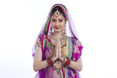 Portrait of beautiful Indian bride greeting over white background Stock Photo