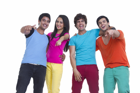 Cheerful young friends pointing at you over white background Banco de Imagens