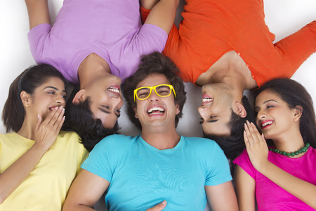 Directly above shot of friends sharing secret while lying over white background