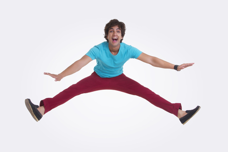 legs apart: Full length portrait of excited young man jumping over white background Stock Photo