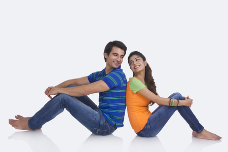 Full length side view of young couple sitting back to back over white background