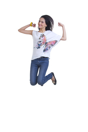 cheer full: Full length portrait of excited young woman jumping over white background Stock Photo