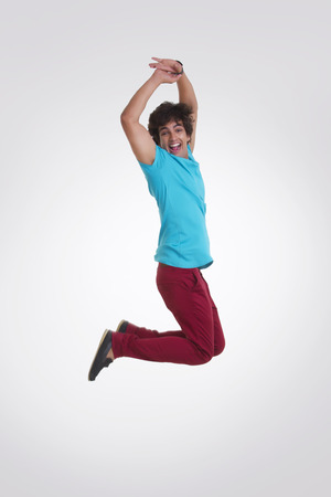 Full length side view of excited young man jumping over white background Stock Photo