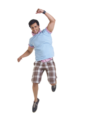 Full length of excited young man jumping over white background