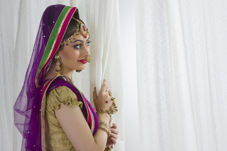Side view of smiling bride standing by window at home