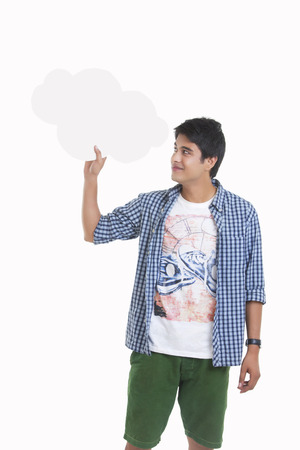 Young man holding thought bubble over white background Stock Photo