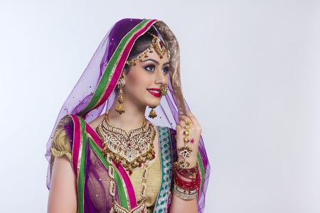 Beautiful Indian bride looking away against gray background