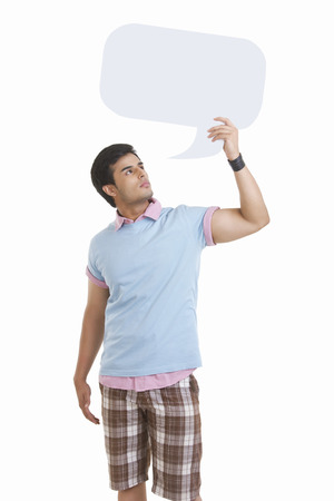 Thoughtful young man holding speech bubble over white background