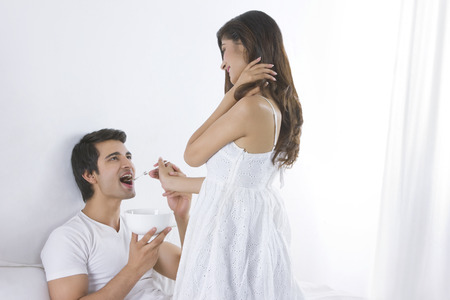 Happy young woman feeding man in bedroom Stock Photo