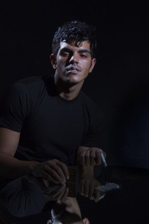 Portrait of young drug addict with cocaine and rolled up banknote