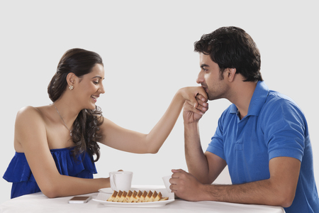 off shoulder: Loving man kissing woman on hand while having coffee against white background
