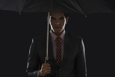 welldressed: Portrait of confident young businessman holding umbrella against black background