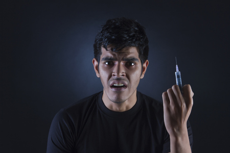 Portrait of confused drug addict with syringe against black background Stock Photo