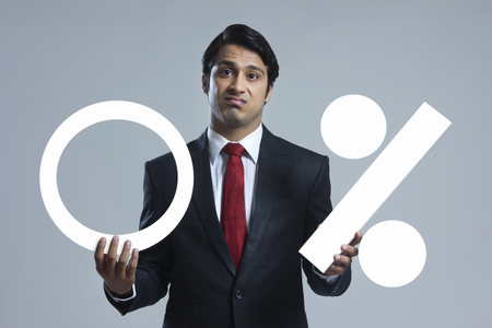 displeased: Portrait of disappointed businessman holding zero percentage sign over gray background