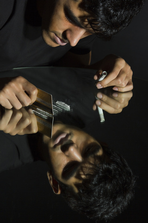 Drug addict cutting cocaine lines with credit card on mirror Stock Photo