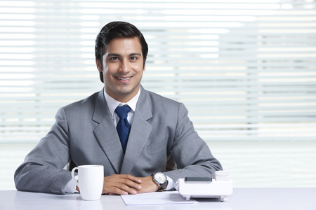 Portrait of smiling businessman sitting at office desk Stock Photo