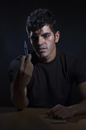 front view: Male drug addict holding syringe
