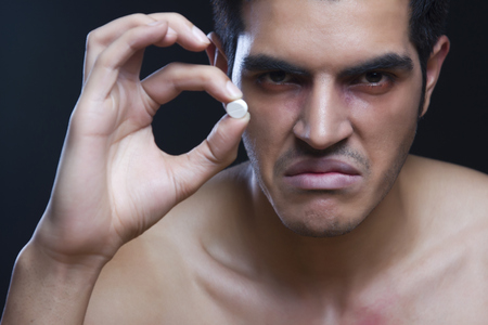 Portrait of angry drug addict holding pill against black background