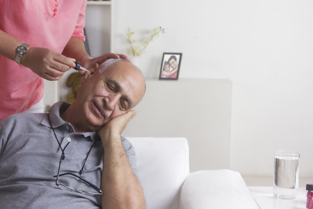 front house: Old man getting ear drops put in