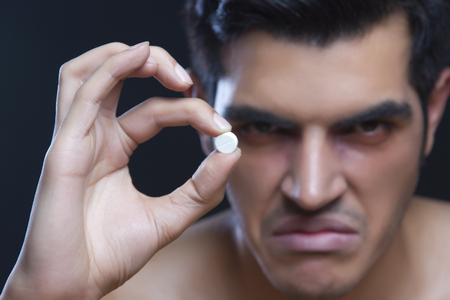 Portrait of angry male drug addict holding pill against black background