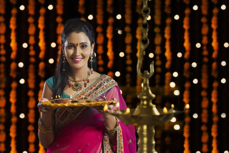 Portrait of woman holding tray of diyas Stock Photo