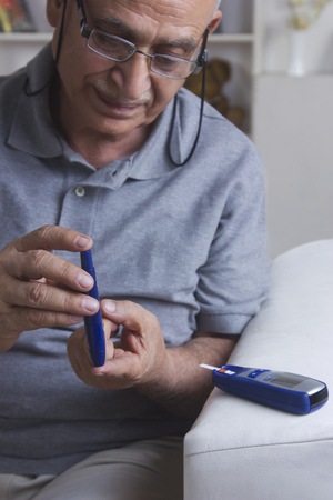 front house: Diabetic old man testing blood sugar Stock Photo