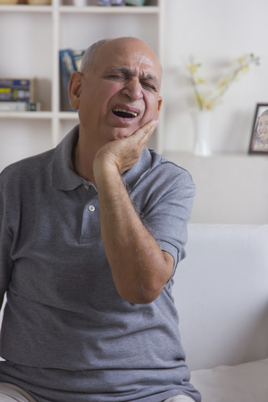 front house: Old man with toothache Stock Photo