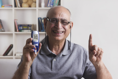 front house: Old man with glucose meter gesturing