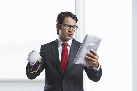welldressed: Businessman spilling coffee while reading newspaper in office