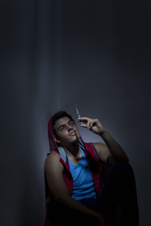 Male drug addict looking at syringe against wall Stock Photo