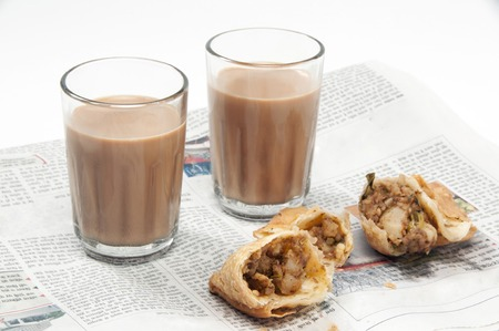 Indian chai with samosas on newspaper isolated over white background Фото со стока