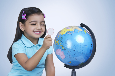 finding out: Cheerful girl exploring globe with magnifying glass against blue background