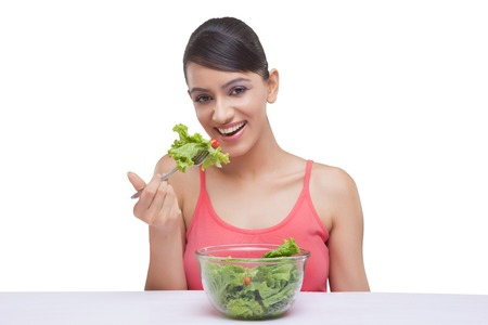 Portrait of smiling young woman eating lettuce over white background