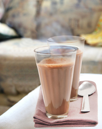 Glasses of morning chai with steel spoon kept on table napkin Stock Photo