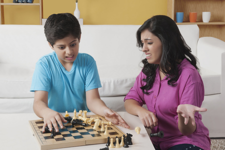 brother sister fight: Sister and brother playing chess in living room