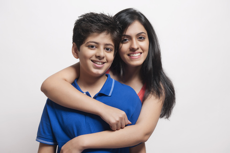 sleeveless top: Portrait of Sister with arms around her brother looking at camera and smiling