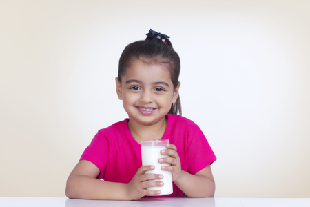 Portrait of girl with glass of milk against colored background