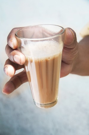 Close-up of mans hand holding glass of chai