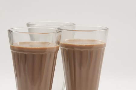 Close-up of chai glasses with an empty glass isolated over white background
