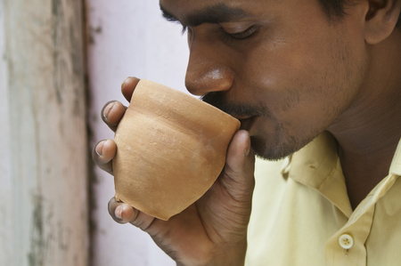Close-up of Indian mid adult man having morning tea in traditional cup made of mud
