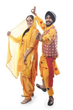 religious clothing: Portrait of Sikh couple doing bhangra dance
