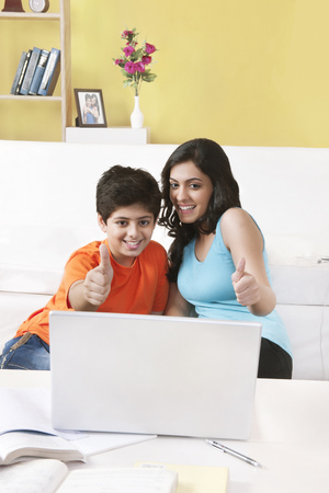 sleeveless top: Sister and brother watching laptop showing thumbs up gesture