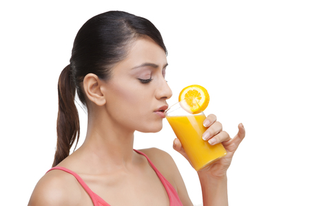 Close-up of young woman drinking orange juice over white background