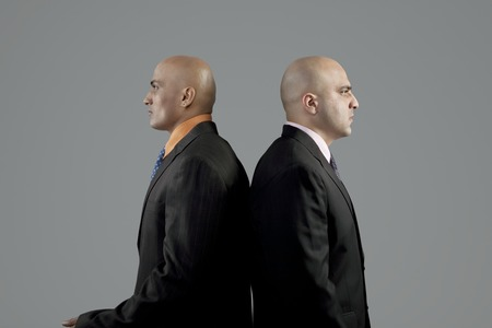 rival: Two bald businessmen standing back to back Stock Photo