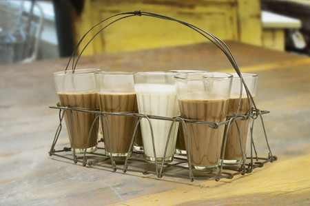 metal grid: Glass of milk kept among chai in metal grid tray on a wooden surface Stock Photo