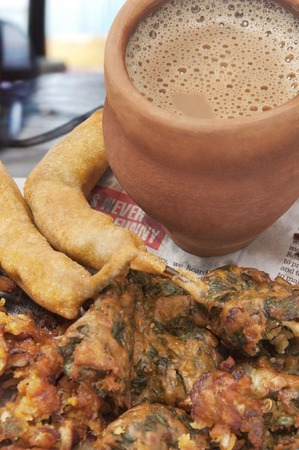 Close-up of Indian pakoras and bhajiyas with chai in traditional cup made of mud on a newspaper